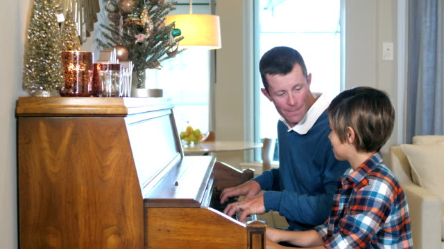 father and son playing piano, christmas decorations - 8 9 years stock videos & royalty-free footage