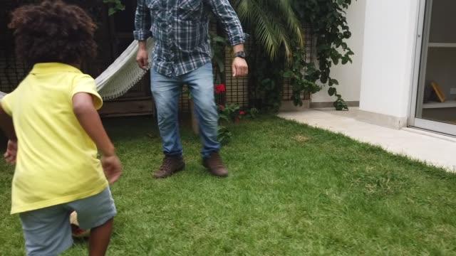 vídeos de stock, filmes e b-roll de pai e filho que jogam o futebol no quintal - messing about