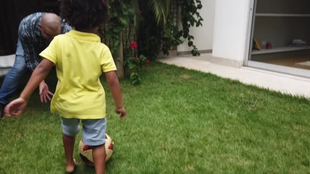father and son playing soccer in backyard - kicking stock videos & royalty-free footage
