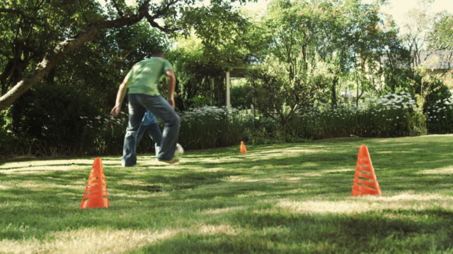WS LA Father and son (8-9) playing soccer in yard / Seattle, Washington, USA