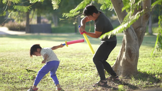 vídeos y material grabado en eventos de stock de padre e hijo jugando a la lucha con la espada en el parque, al aire libre. - son