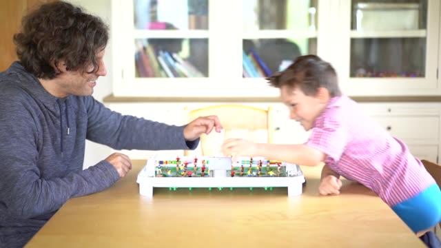 vídeos y material grabado en eventos de stock de padre e hijo jugando al fútbol de mesa en casa - son