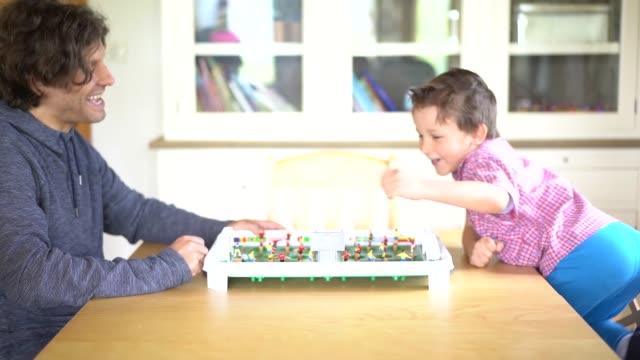 vídeos de stock, filmes e b-roll de pai e filho jogando futebol de mesa em casa - termo esportivo