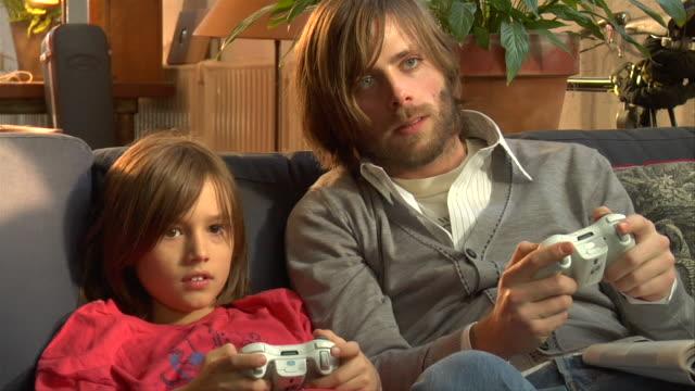 vídeos de stock e filmes b-roll de ms, father and son (8-9) playing video game - barba