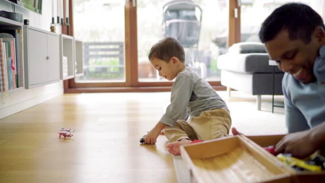 stockvideo's en b-roll-footage met father and son playing - op de grond zitten