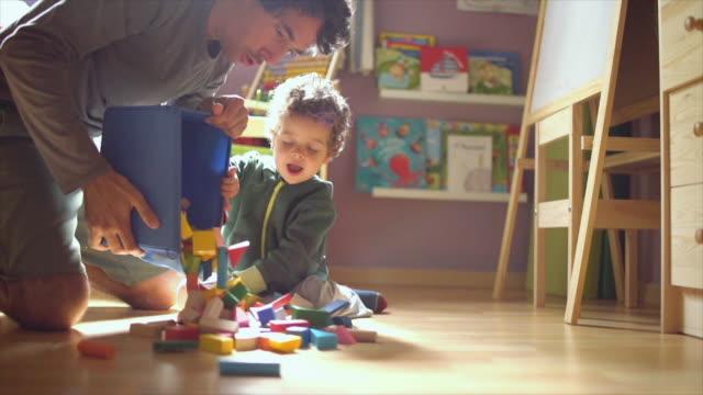 vídeos de stock, filmes e b-roll de father and son playing - bloco de construção