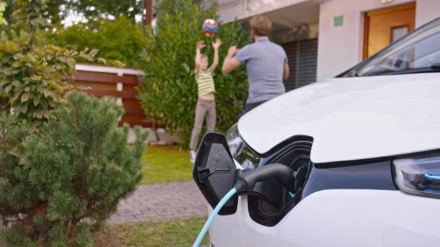 vídeos de stock e filmes b-roll de slo mo father and son playing while car is charging - carregar atividade