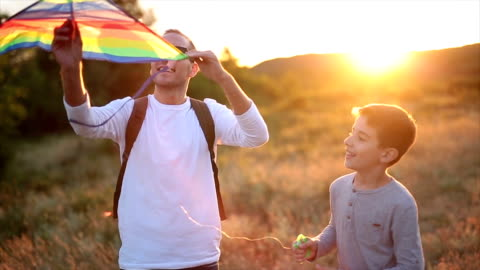 father and son playing with a kite in nature - leisure activity stock videos & royalty-free footage