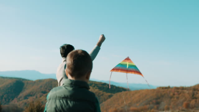 father and son playing with a kite in nature - kid with kite stock videos & royalty-free footage