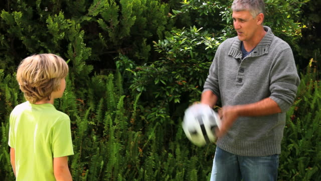 Father and son playing with football in garden / Cape Town, Western Cape, South Africa