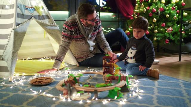vidéos et rushes de père et fils jouant avec le nouveau jouet de train devant l'arbre de noël - son