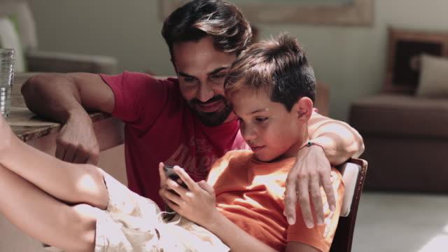 vídeos de stock, filmes e b-roll de father and son playing with smart phone - família de duas gerações