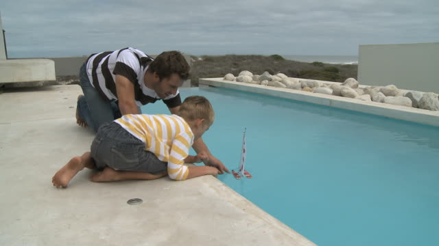 ws father and son (6-7) playing with toy boat on poolside / cape town south africa - おもちゃ点の映像素材/bロール