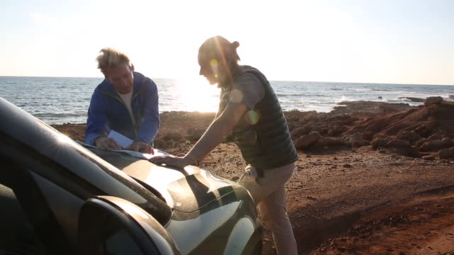 Father and son plot route on map, on vehicle hood