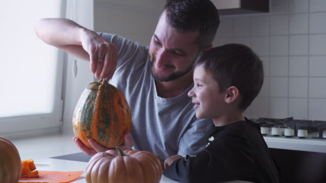 father and son preparing jack-o-lantern for halloween party - brown hair stock videos & royalty-free footage