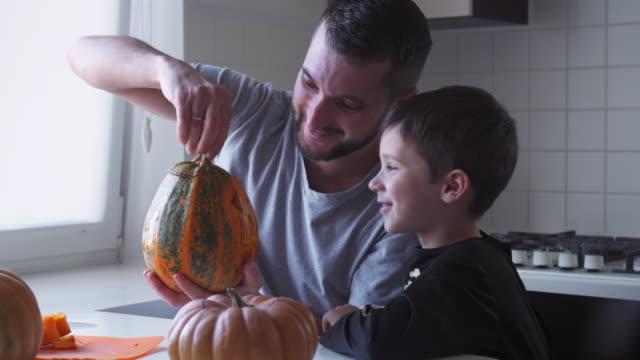 vídeos y material grabado en eventos de stock de padre e hijo preparando gato-o-linterna para fiesta de halloween - son