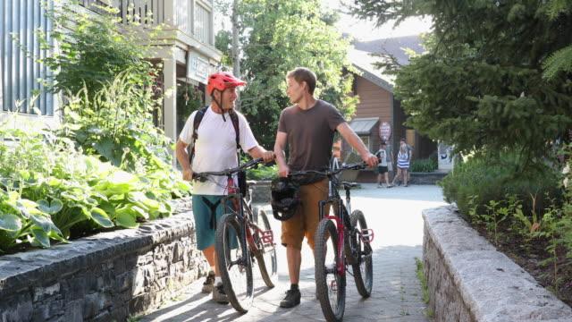 父と息子は村を通ってマウンテンバイクをプッシュ - pushing点の映像素材/bロール