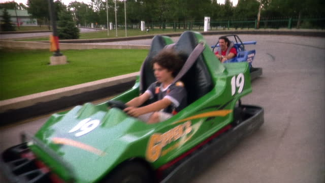 father and son racing go-carts around bend in track - number 3 stock videos & royalty-free footage