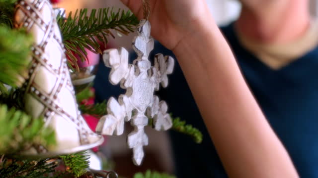Father and son reach to hang ornaments on Christmas tree