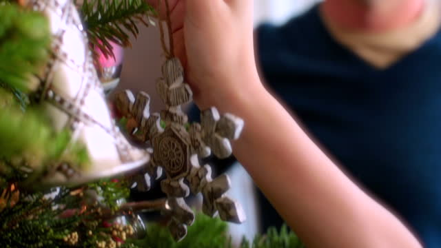 stockvideo's en b-roll-footage met father and son reach to hang ornaments on christmas tree - kerstboom versieren