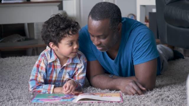 vídeos de stock, filmes e b-roll de um pai e um filho lêem um livro junto - união