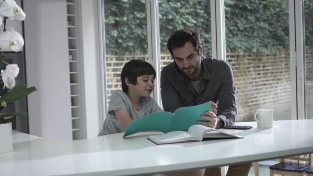vídeos de stock e filmes b-roll de father and son reading a book - genderblend