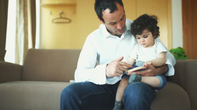 father and son reading a book. - curly stock videos & royalty-free footage