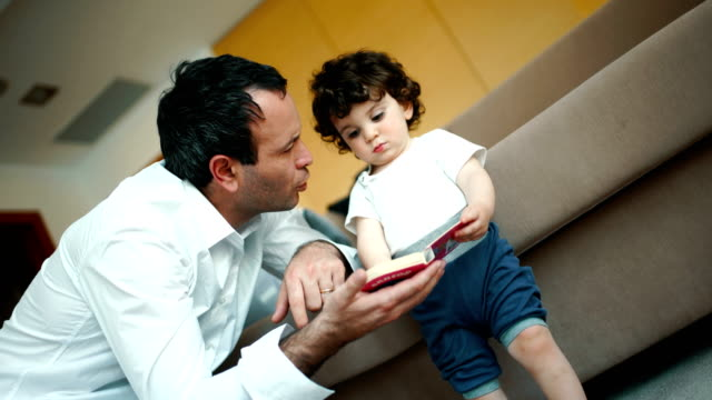 father and son reading a book. - brown hair stock videos & royalty-free footage