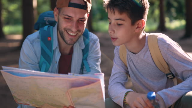 father and son reading map in forest - father and son stock videos & royalty-free footage
