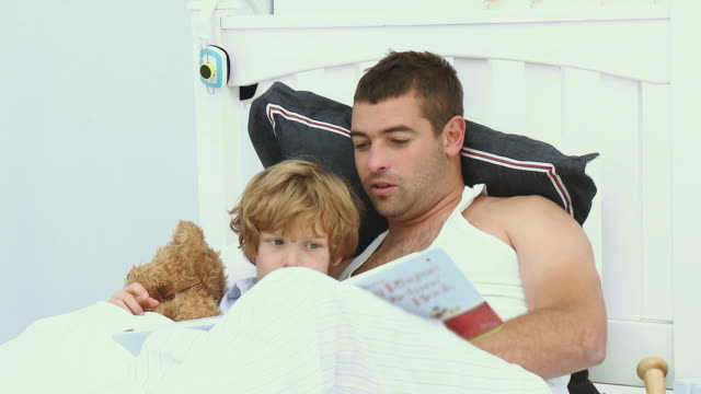 vídeos y material grabado en eventos de stock de ms father and son (6-7) reading together on bed / cape town, south africa - recostarse