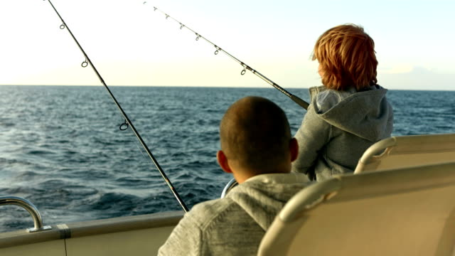 stockvideo's en b-roll-footage met hd: father and son reeling in a fish - nautical vessel
