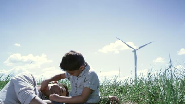ms father and son relaxing in wind farm / toulouse, midi-pyrenees, france - ligga ner bildbanksvideor och videomaterial från bakom kulisserna