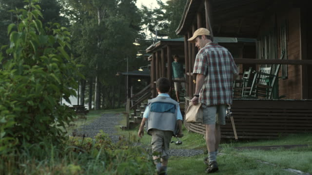 ws father and son (6-7) returning from fishing to sporting camp, south arm, maine, usa - capanna di legno video stock e b–roll