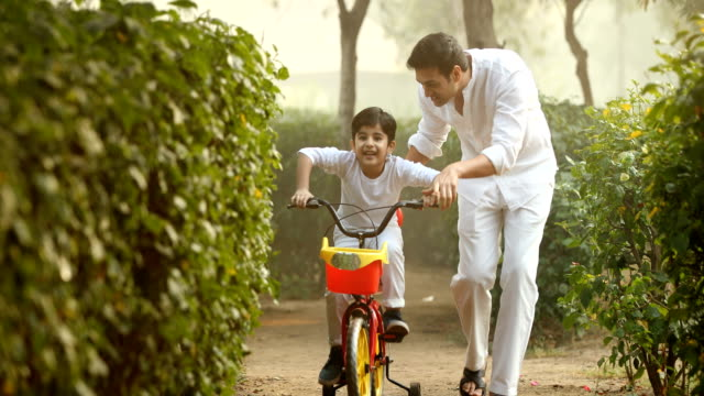 ms father and son riding bicycle in park / india - indian ethnicity stock videos & royalty-free footage