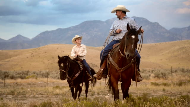 father and son riding horses - cultura americana video stock e b–roll