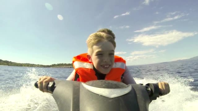father and son riding jet-ski - ski stock videos & royalty-free footage