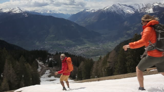father and son run down snow slope towards valley below - sliding stock videos and b-roll footage