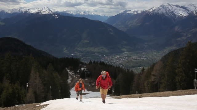 Father and son run up steep snow slope on mountainside