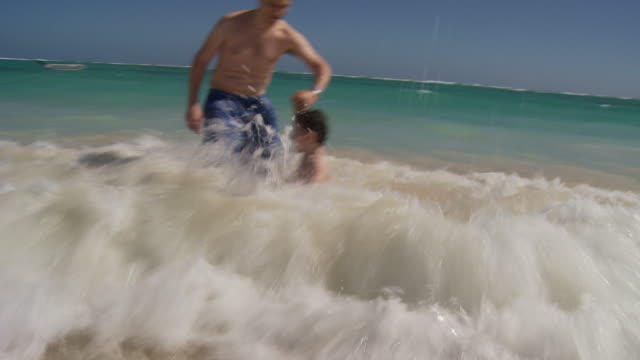 vídeos de stock, filmes e b-roll de ms, cu, father and son (2-3) running in ocean waves, punta cana, dominican republic - vadear