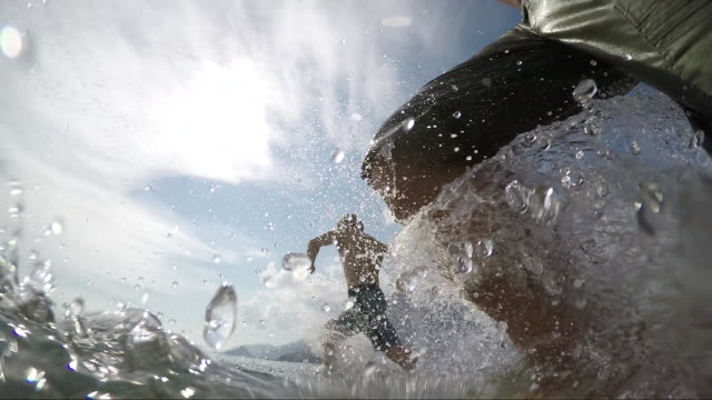 POV of father and son running into the sea