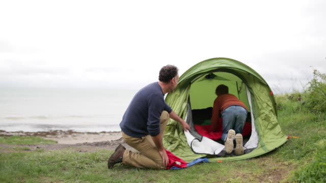 father and son setting up a tent together - 寝袋点の映像素材/bロール