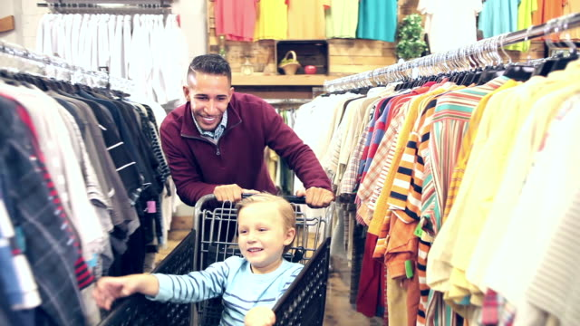 Father and son shopping for clothing, playing with cart