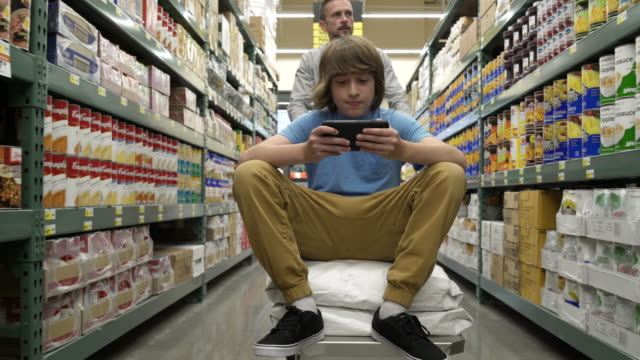 father and son shopping in a warehouse supermarket - supermarkt einkäufe stock-videos und b-roll-filmmaterial