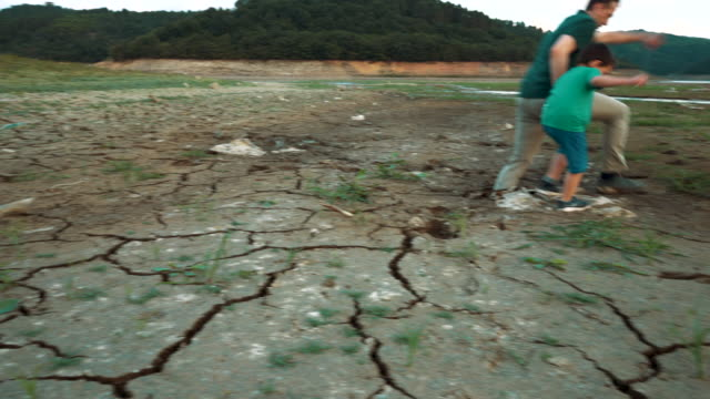 father and son sinking in the swamp while walking on dry lake bed, cracked earth - 4 5 years stock videos & royalty-free footage