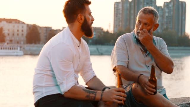 vídeos y material grabado en eventos de stock de padre e hijo sentados junto al río - hijo