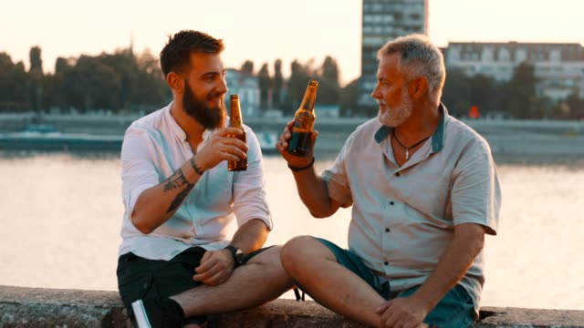 father and son sitting by the river - beer alcohol stock videos & royalty-free footage