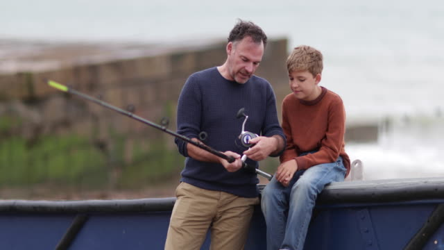 father and son sitting on boat getting ready for fishing trip - hobby video stock e b–roll