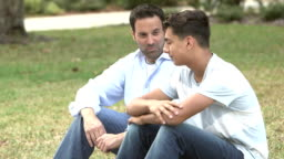 Father and son sitting on lawn, talking
