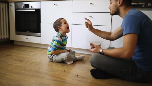 vater und sohn sitzen auf dem boden der küche und spielen mit dem essen - respektlosigkeit stock-videos und b-roll-filmmaterial