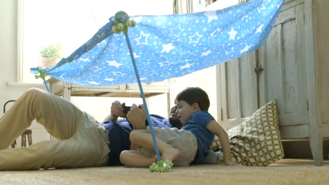 father and son sitting under toy tent. - modern manhood stock videos & royalty-free footage